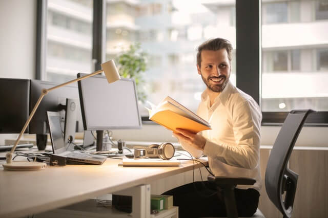 machine learning engineer at AI company happy by desk with book and computer