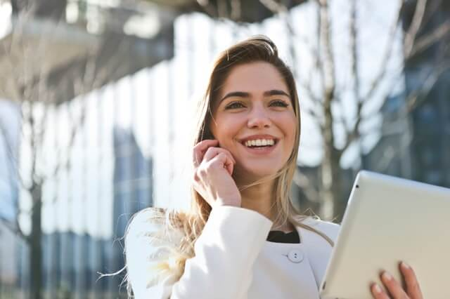 Machine Learning specialist woman happy holding phone and tablet