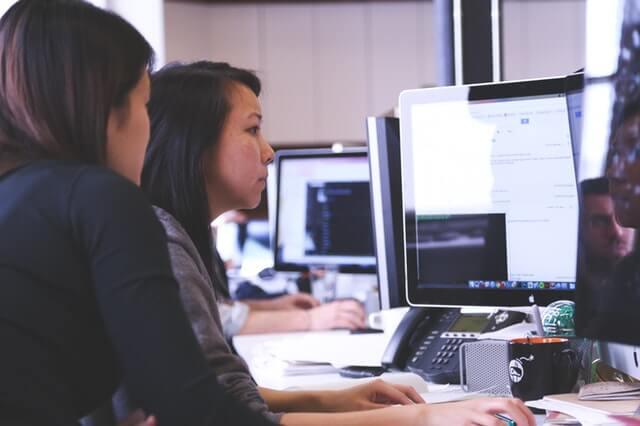 Women working on a computer using econometrics
